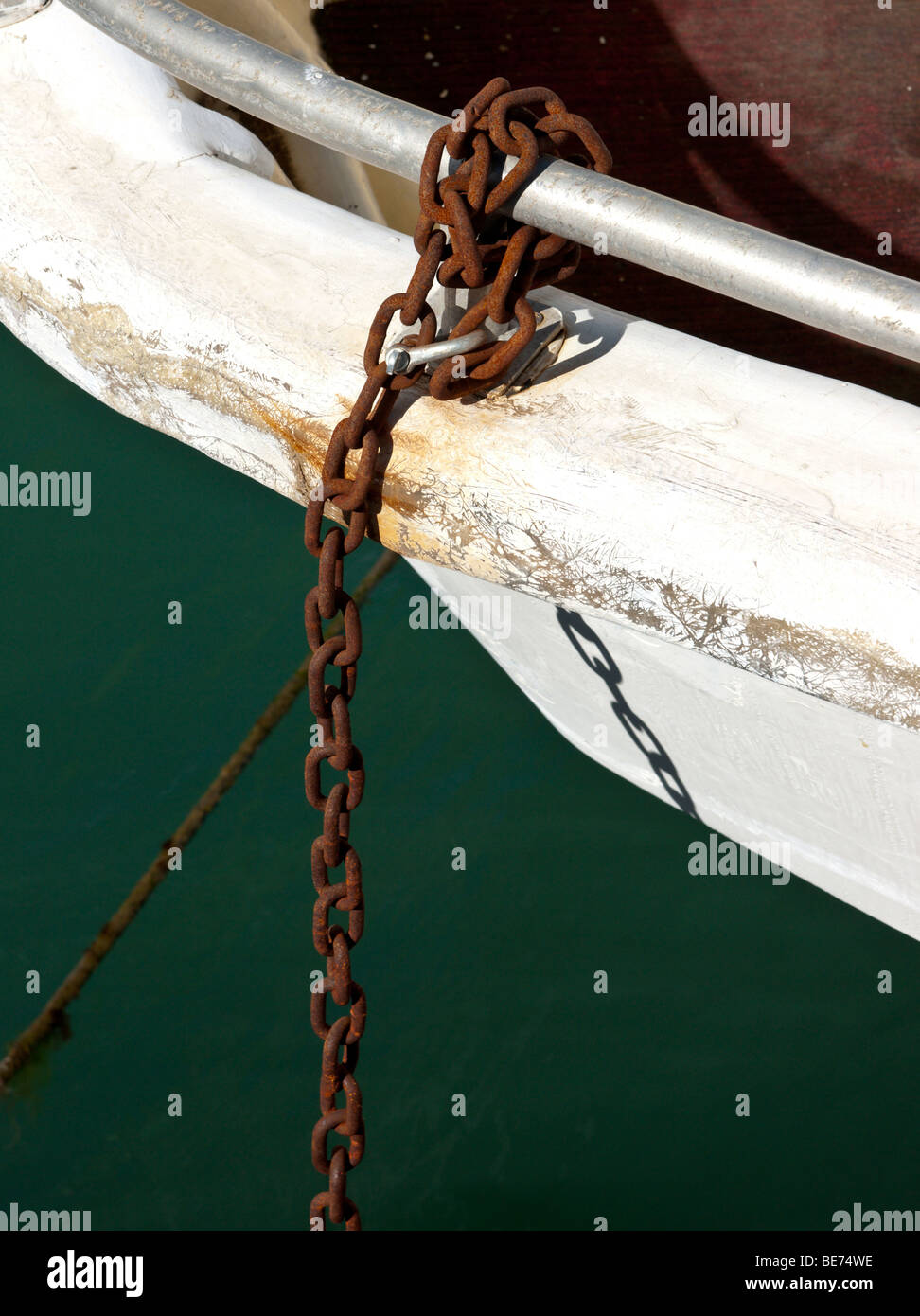Rusty old chain tied to a boat. - Stock Image