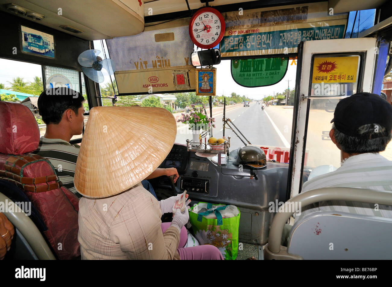 Driver, passenger and cashier looking from a minibus onto the road, Mekong Delta, Vietnam, Southeast Asia - Stock Image