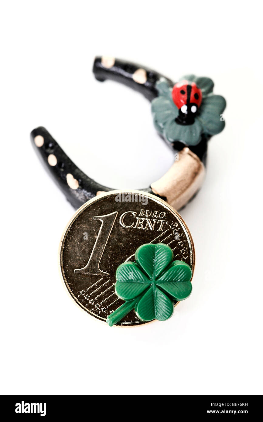 Luck symbols, horseshoe with ladybird and lucky cent with four-leaf clover - Stock Image