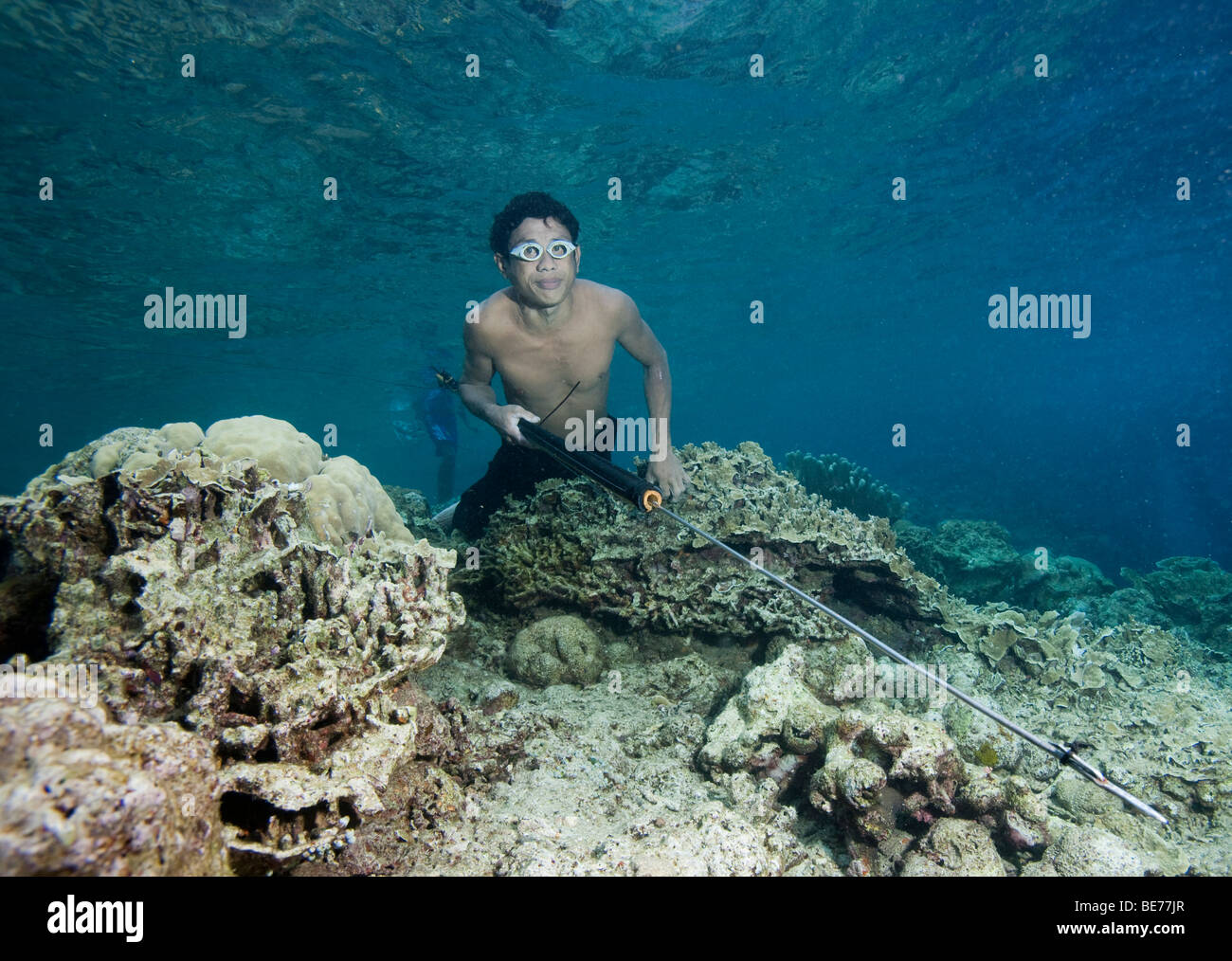 Fisherman hunting fish with a primitive harpoon in the Bunaken National Park, Indonesia, Southeast Asia - Stock Image