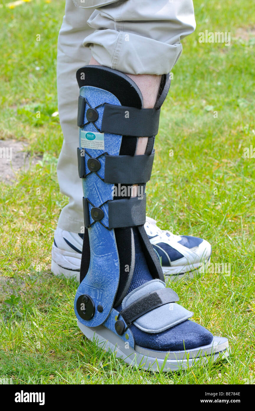 Man with a leg brace after an Achilles tendon rupture - Stock Image