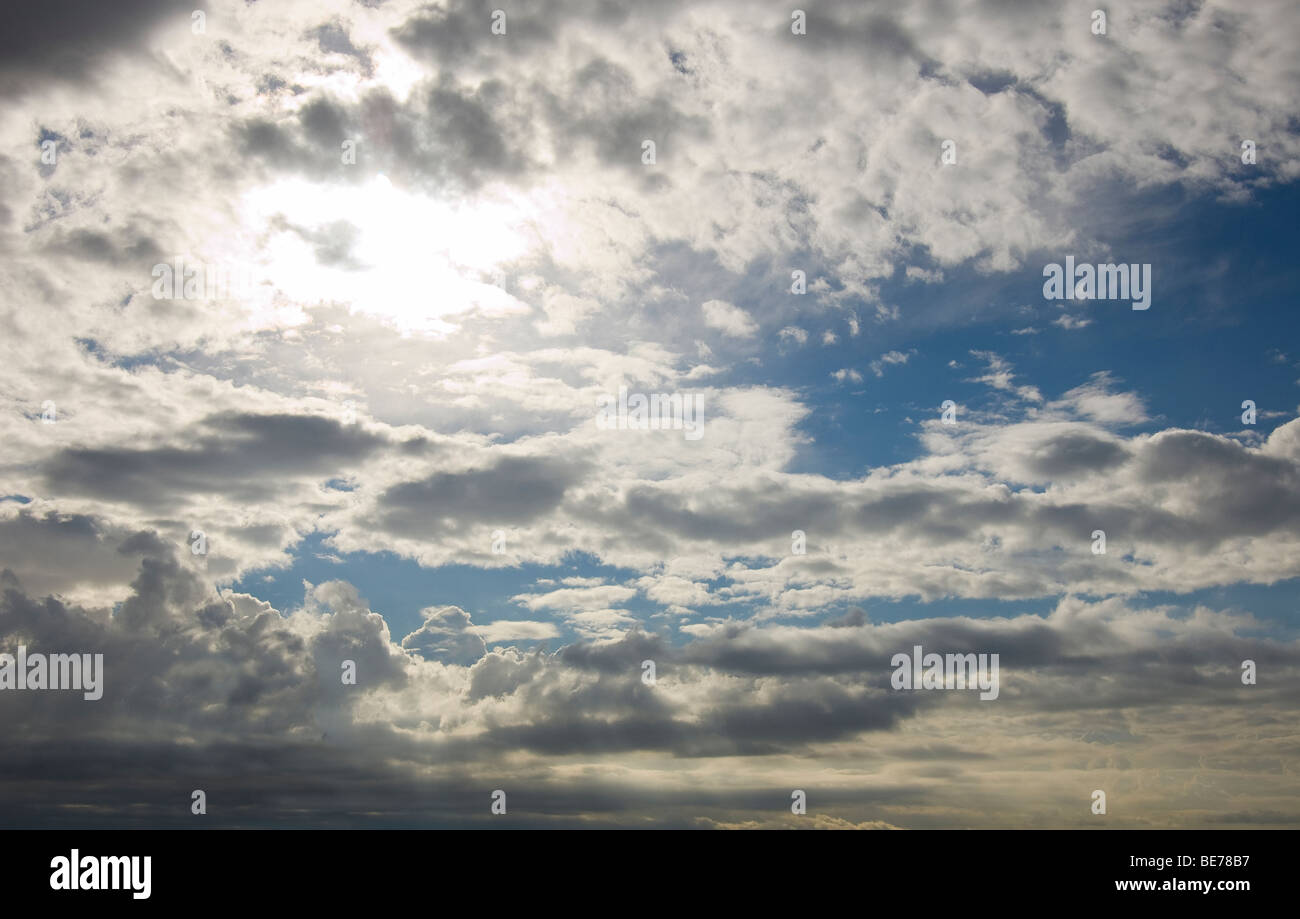 blue cloudy sky, with sun behind clouds - Stock Image