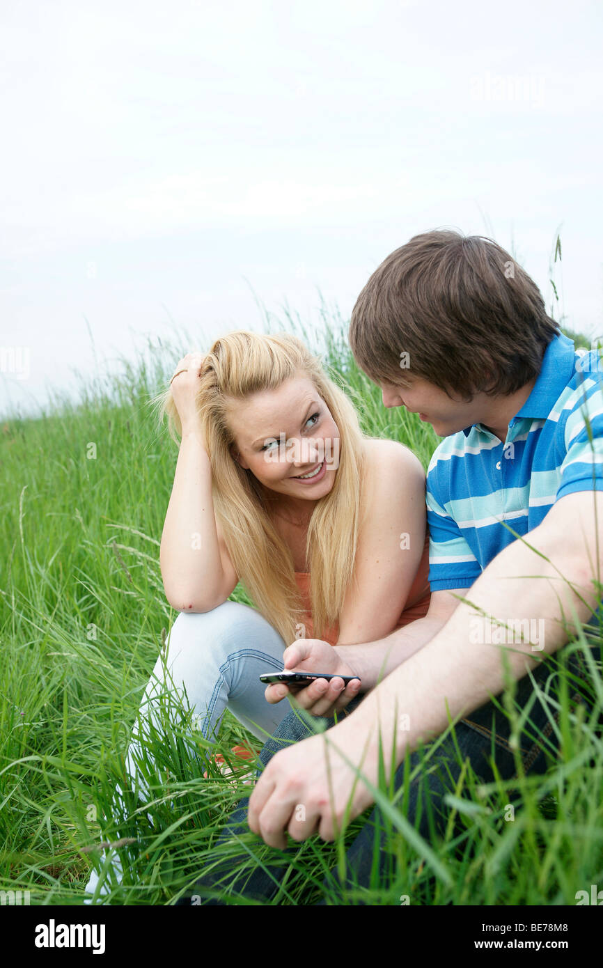 Young couple sitting on a lawn, sending text messages - Stock Image