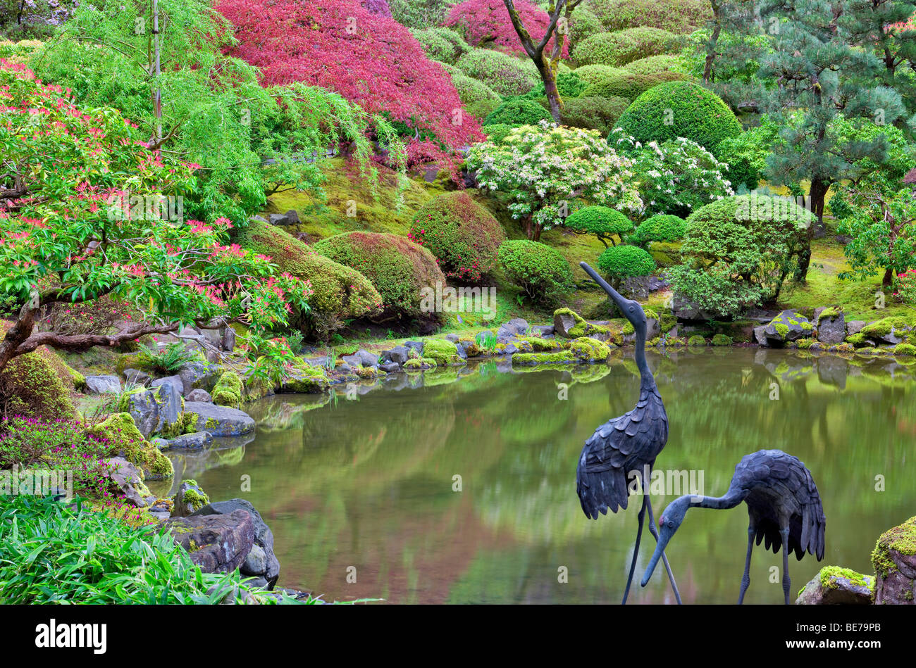 Pond with heron sculpture and early spring growth. Portland Japanese Gardens, Oregon. - Stock Image