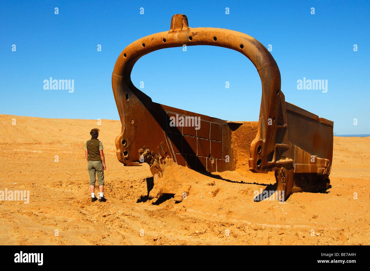 Person standing next to a large bucket of a dragline, De Beers Namaqualand diamond mine, Kleinzee, Northern Cape, - Stock Image