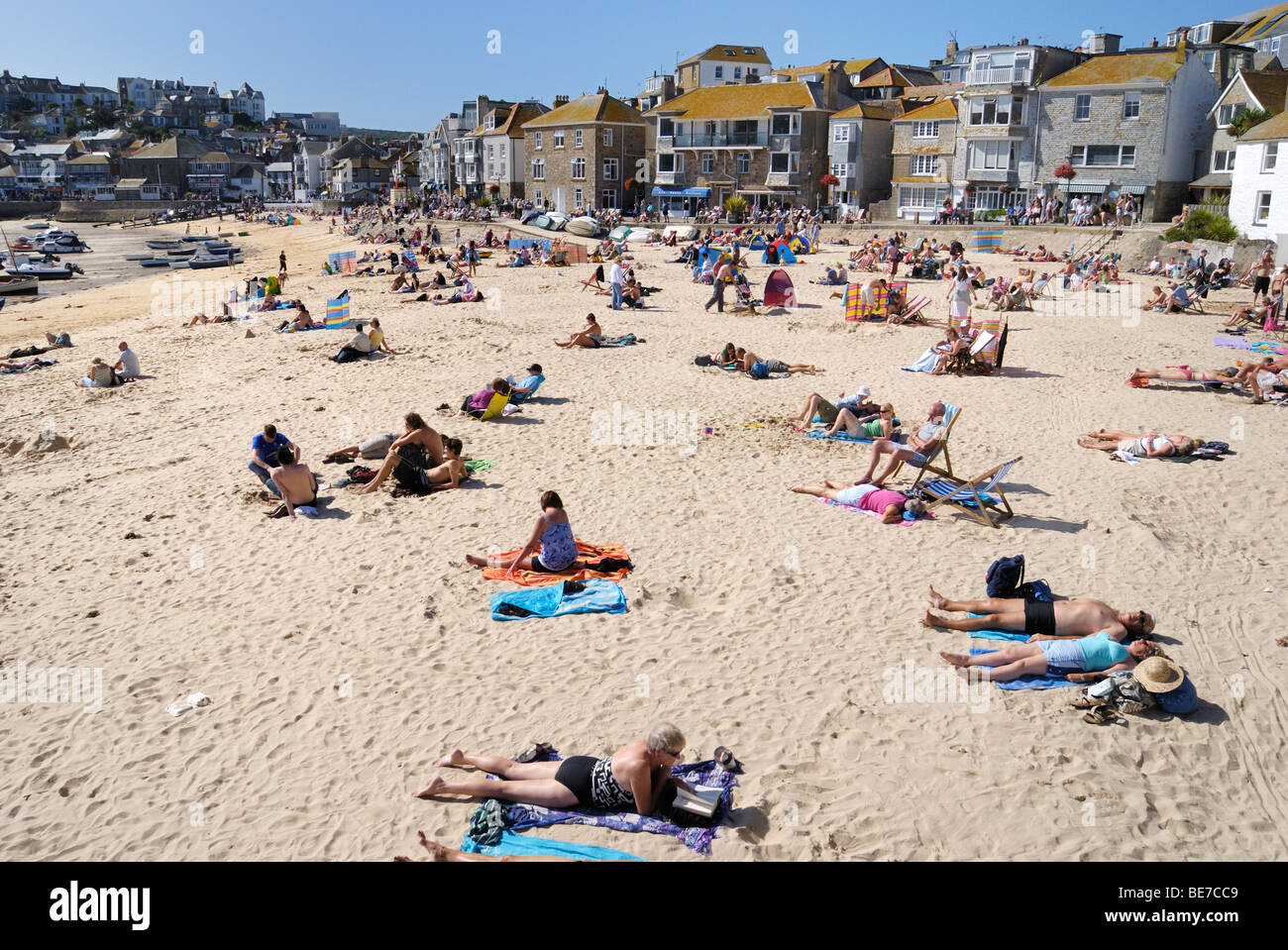 Sunbathers on a sandy beach in St Ives harbour - Stock Image
