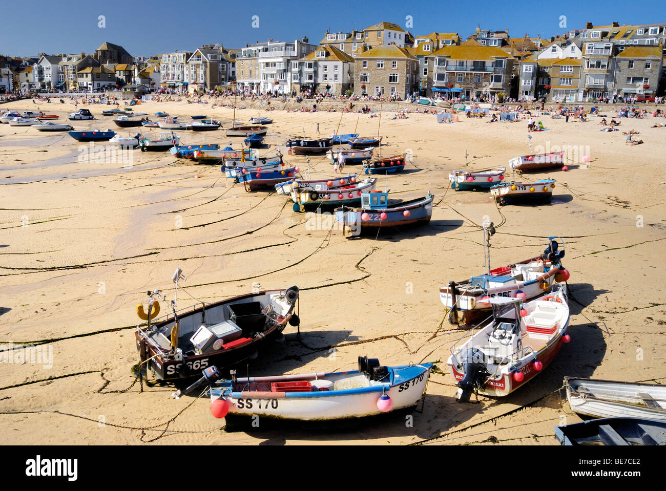 Fishing boats beached on the sand in a harbour at low tide Stock Photo