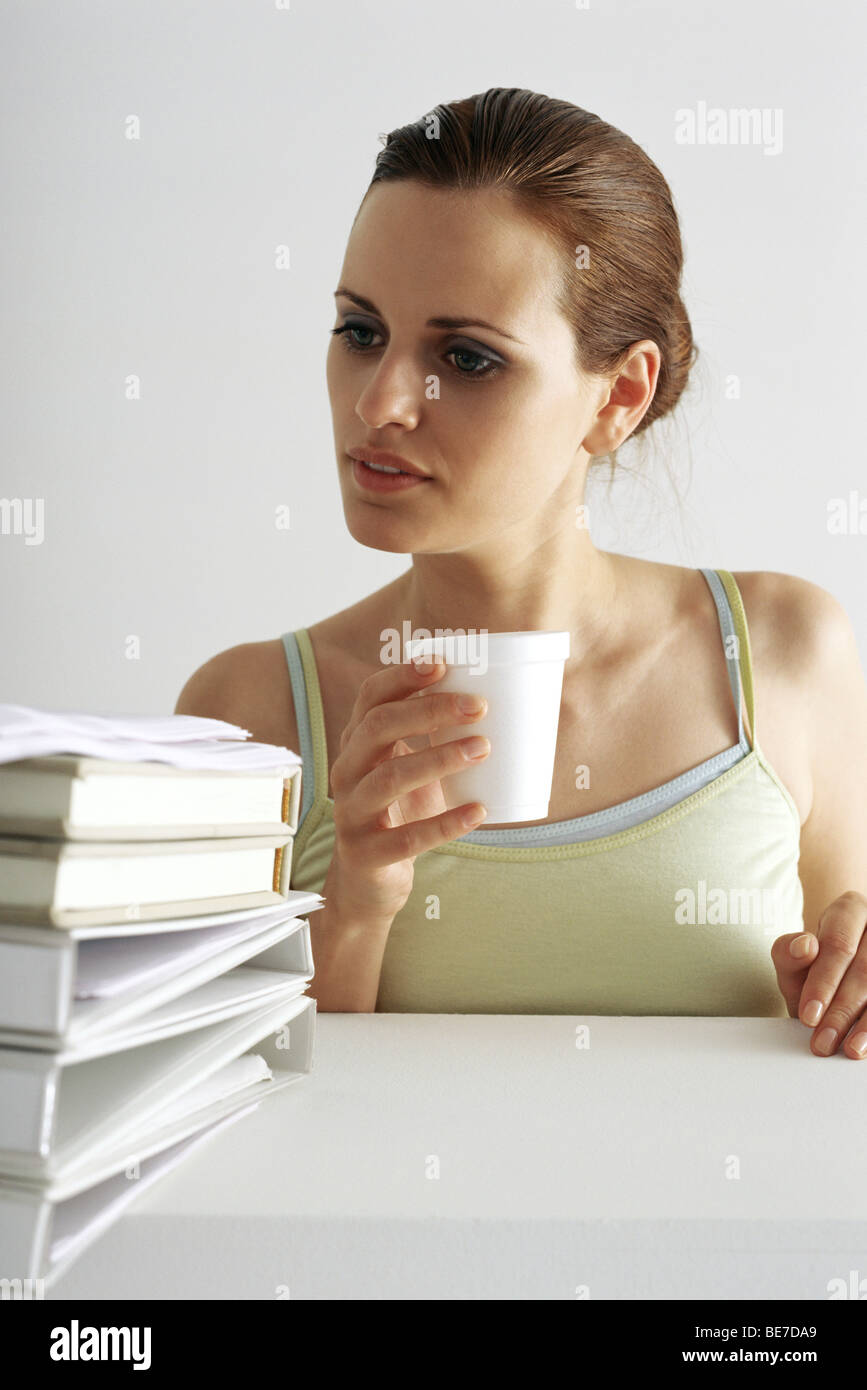 Woman on break looking with curiosity at stack of books and binders - Stock Image