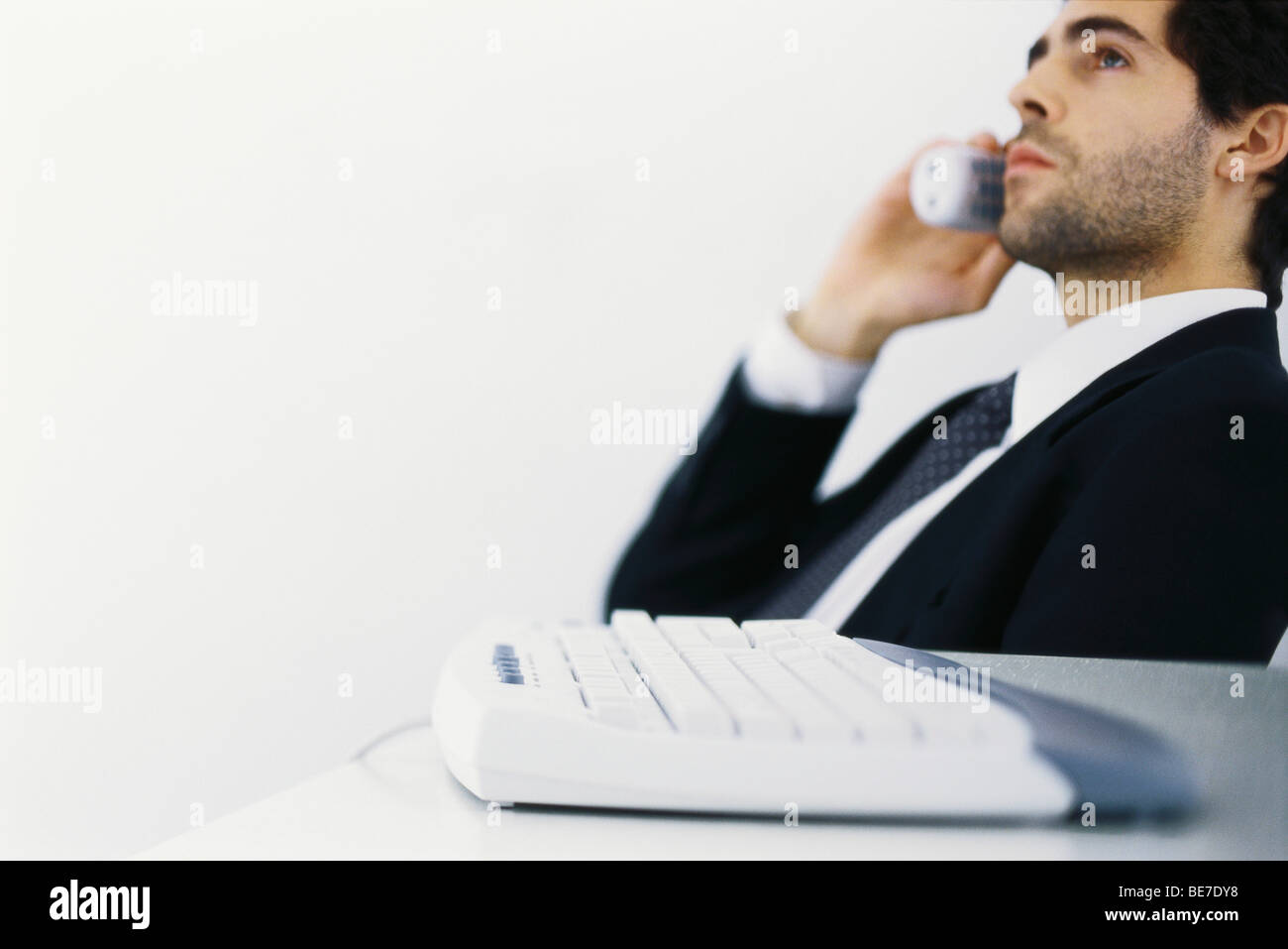 Businessman on phone call, leaning back, looking away - Stock Image