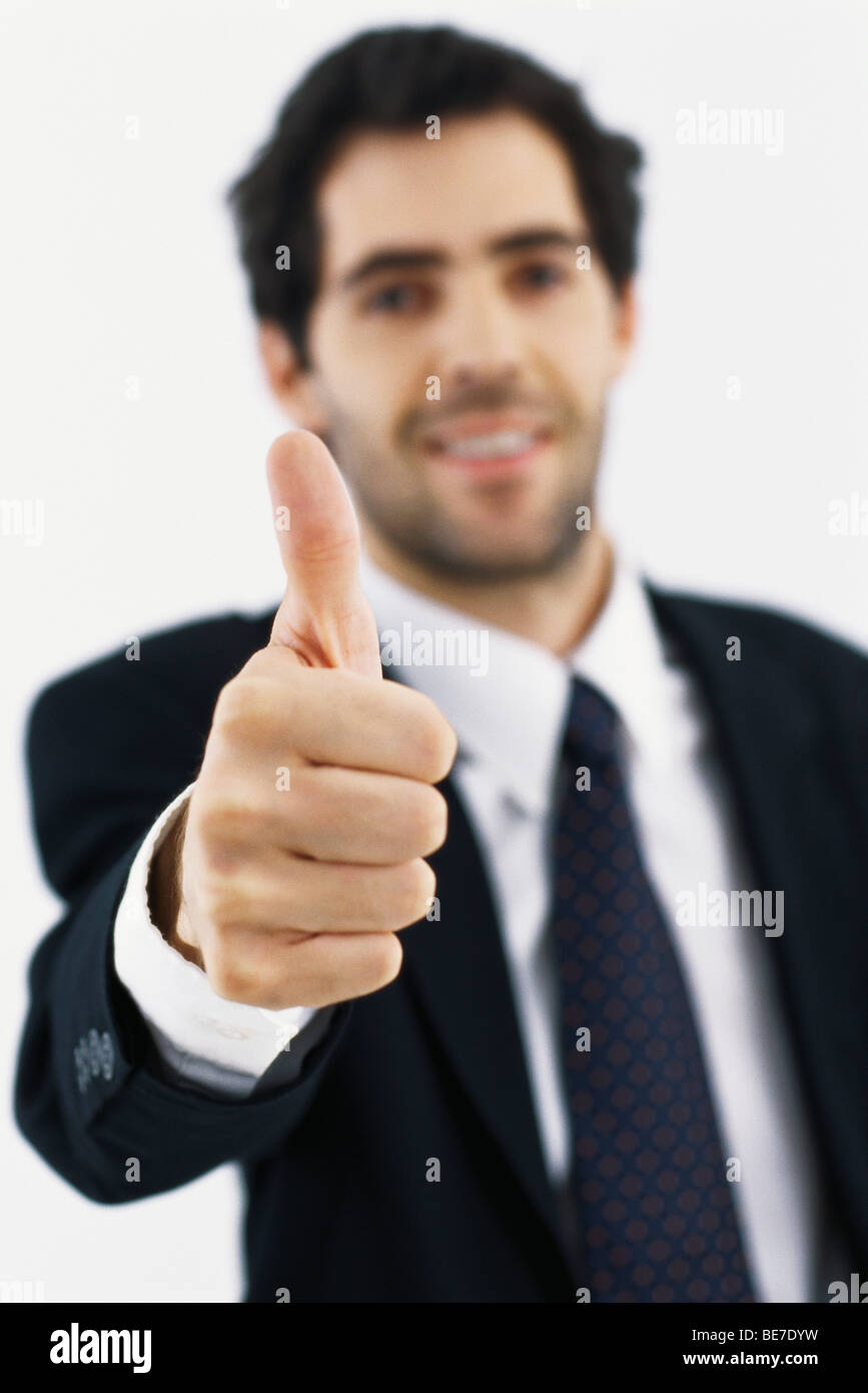 Businessman giving thumbs up - Stock Image