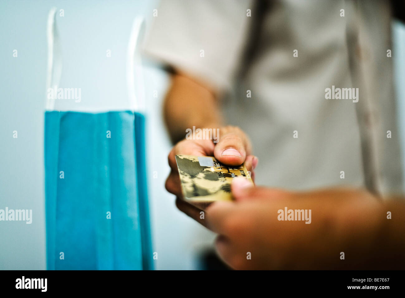 Man paying for purchase with credit card, cropped, close-up - Stock Image