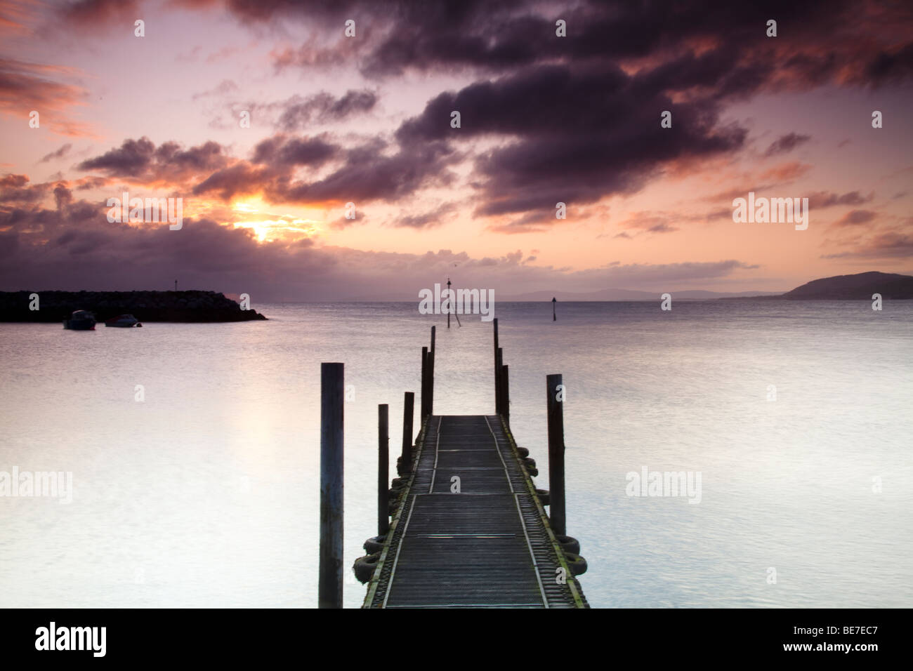 Looking out along the jetty walkway in Rhos on sea harbour at sunrise. Stock Photo