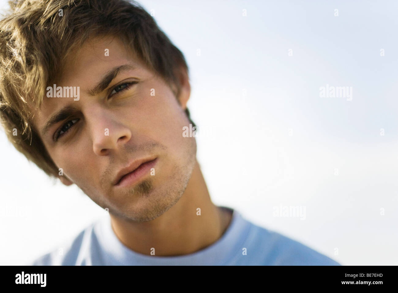 Young man looking at camera with head tilted and brow furrowed - Stock Image