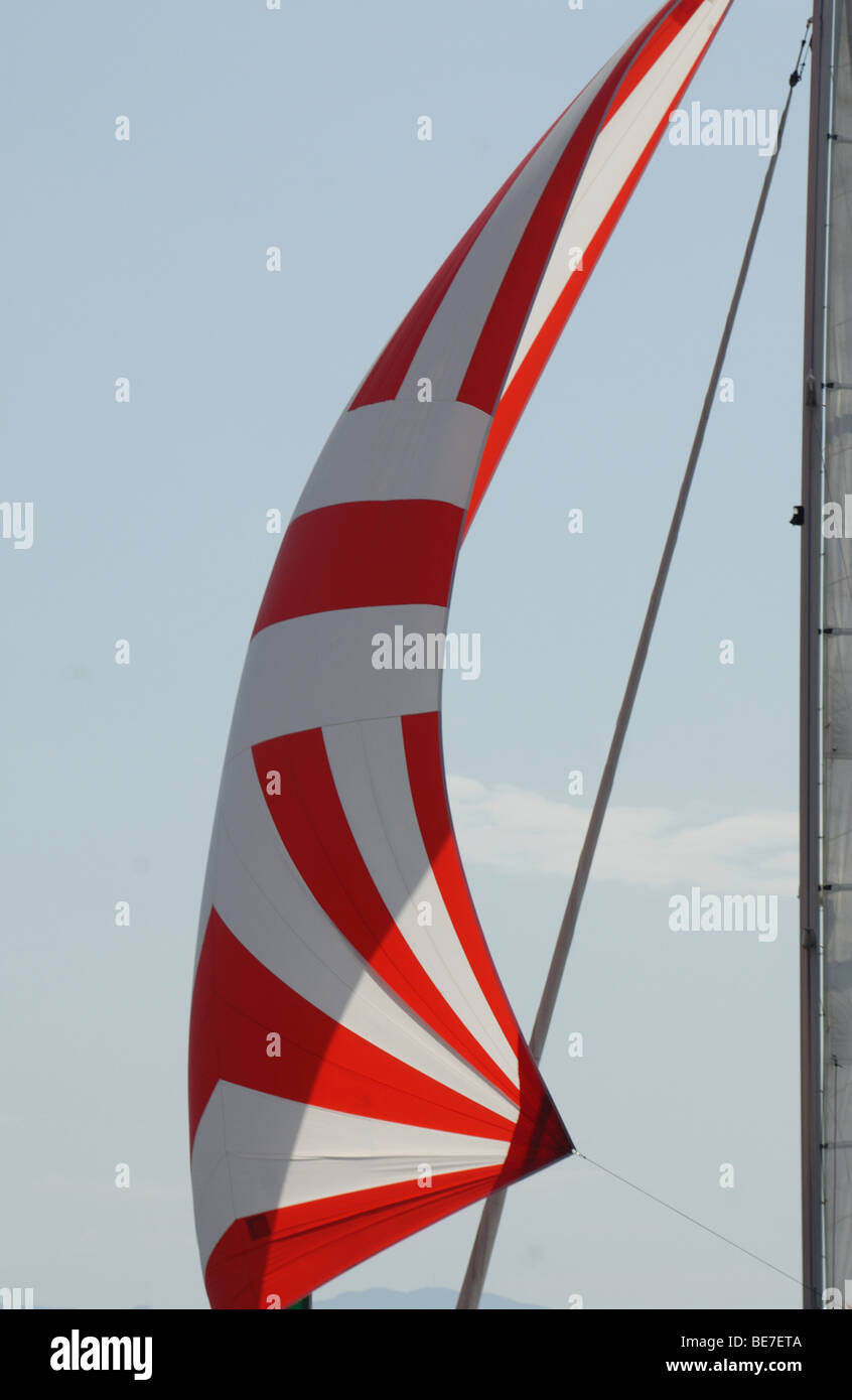 red and white sail of sailboat - Stock Image