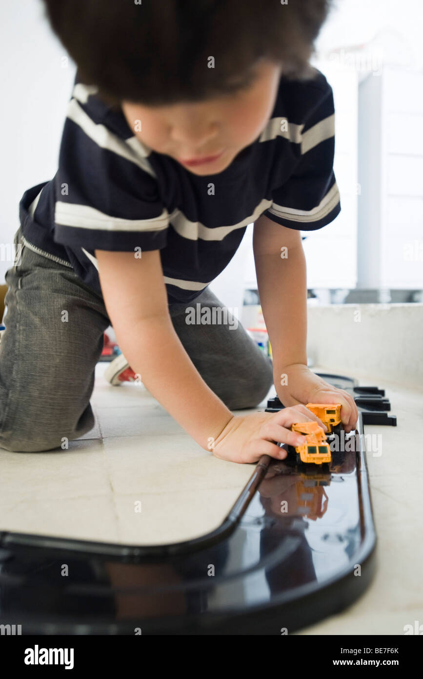 Little boy playing with cars on plastic track - Stock Image