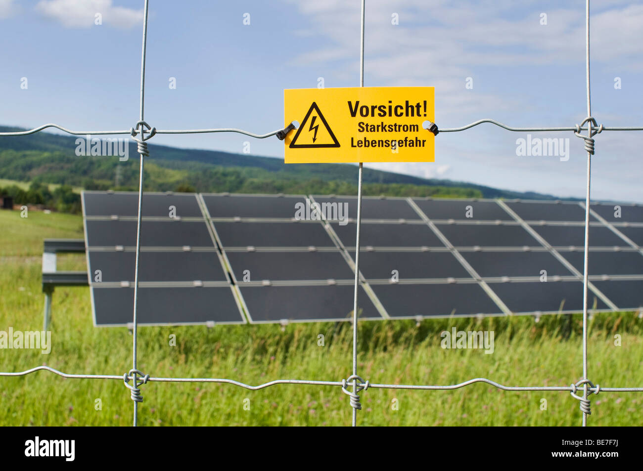 Photovoltaic, modules directed on different stands or racks behind protection fence with danger sign reading Vorsicht - Stock Image