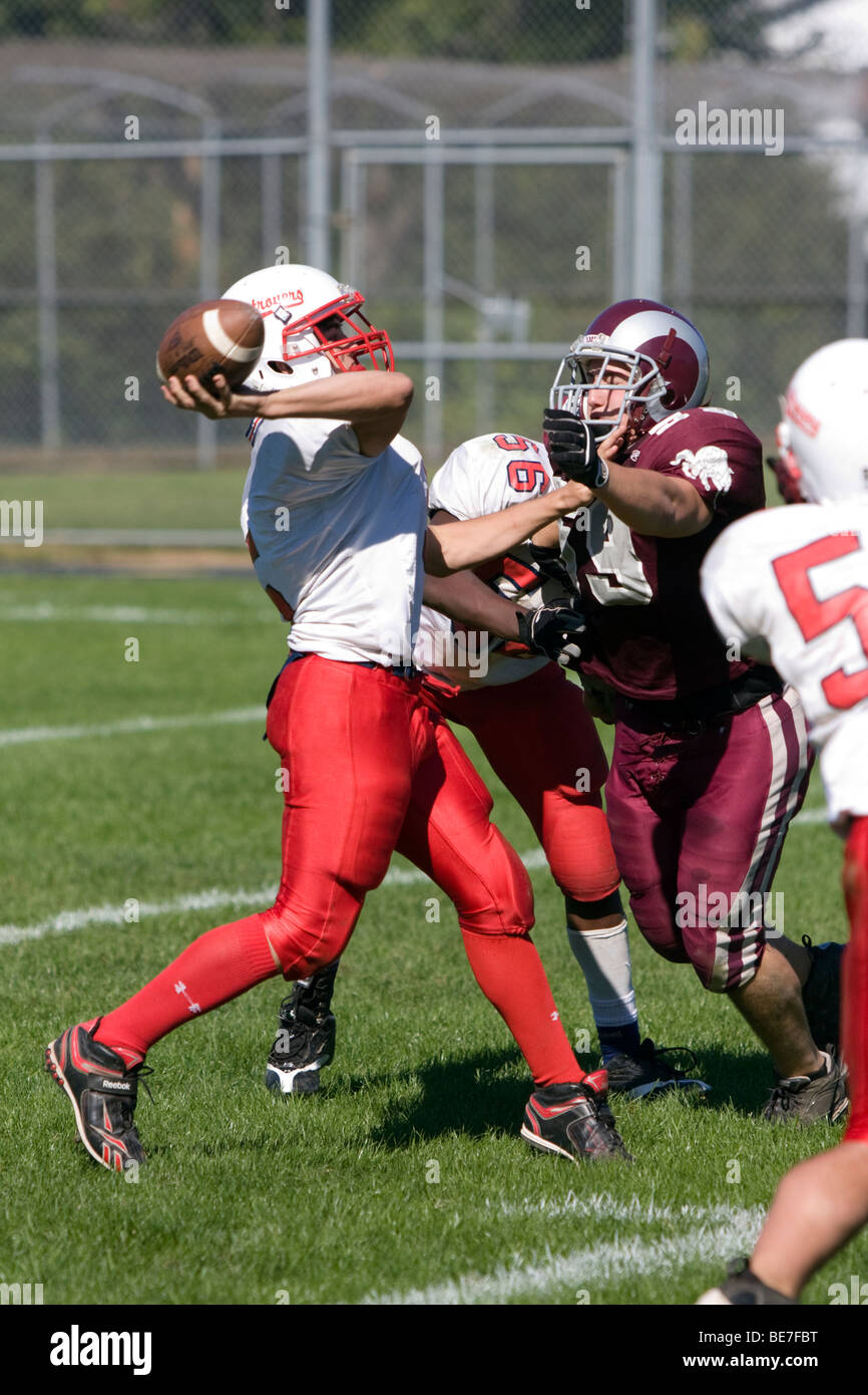 A Quarterback throws the ball as the defense rushes in - American Football - Stock Image