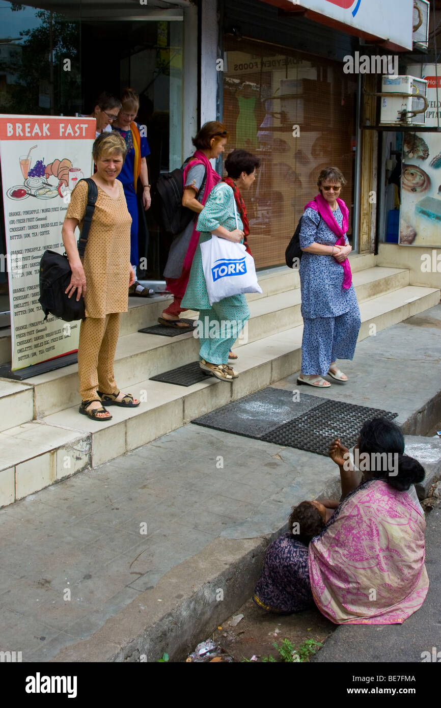 Beggar and western tourists in Pondicherry India Stock Photo