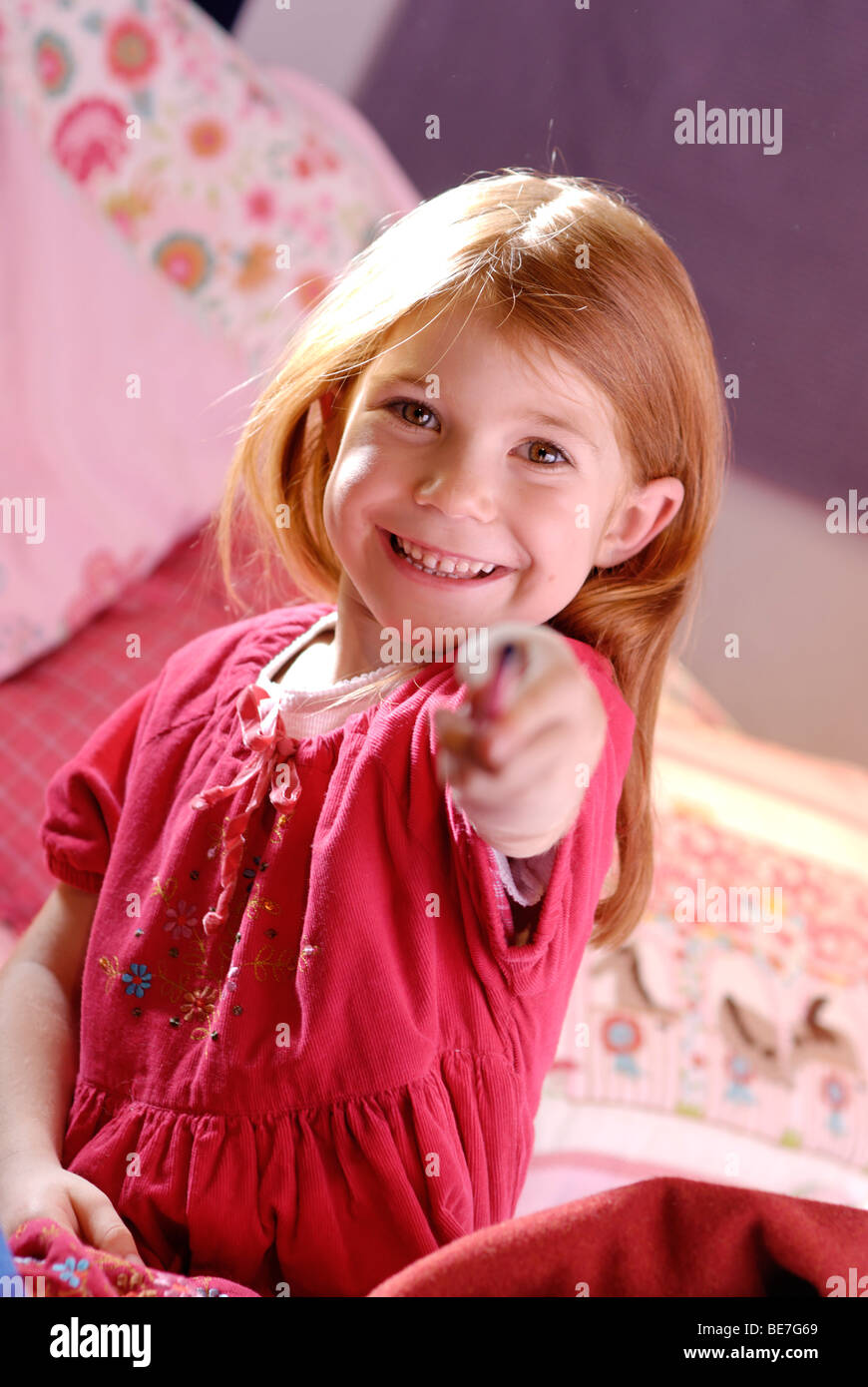 Little girl holding a pen in her hand - Stock Image