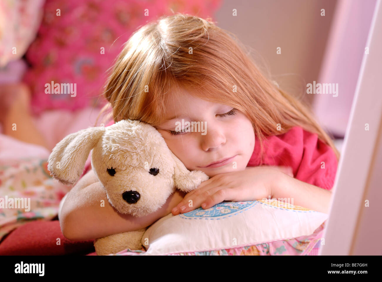 Little girl sleeping with a stuffed toy dog - Stock Image