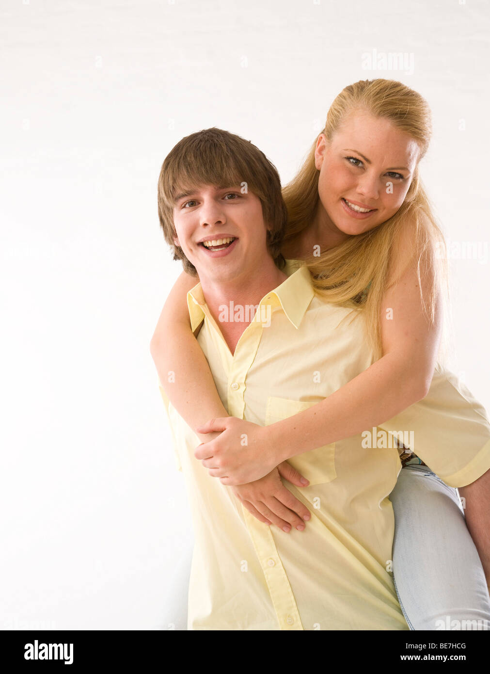 Young man carrying young woman piggyback, laughing - Stock Image