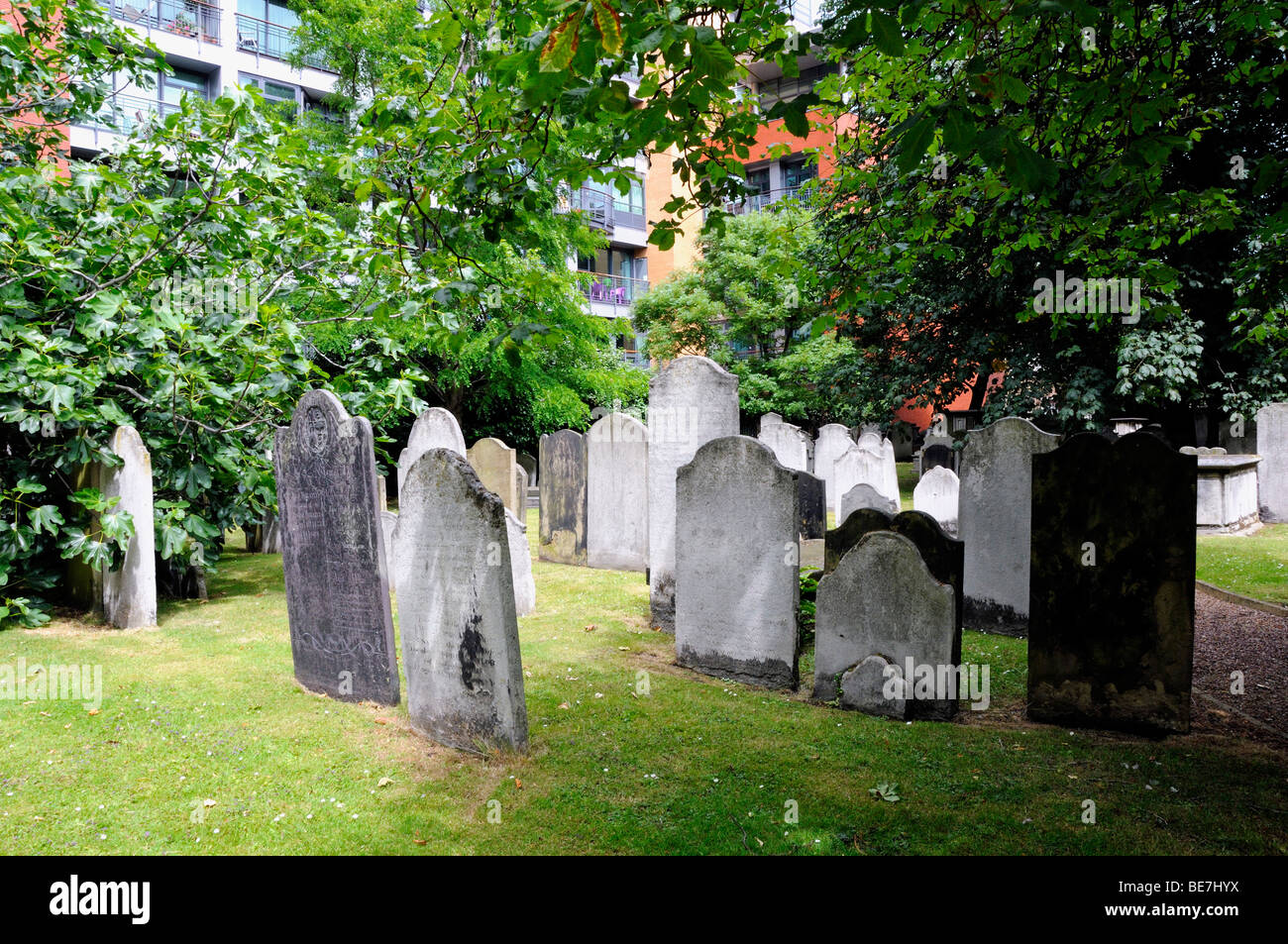 Gravestones Bunhill Fields with flats behind Islington London England UK - Stock Image