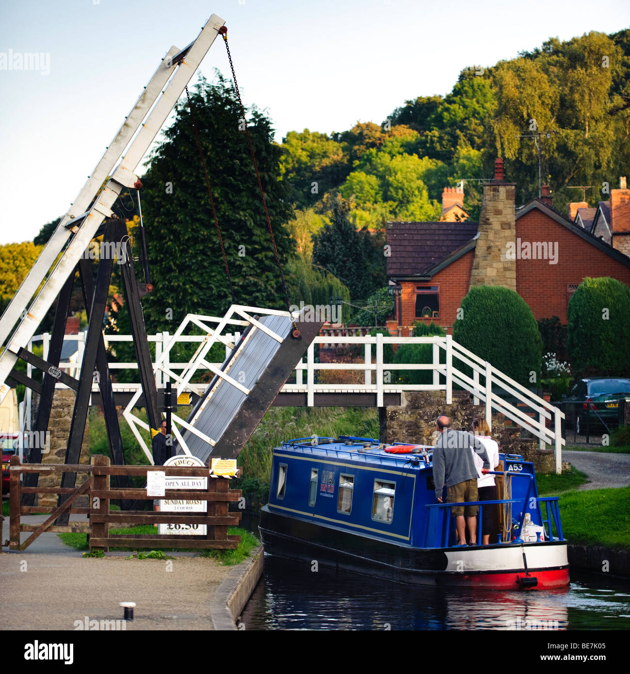 Narrowboat passing under a tilting lifting bridge on the Llangollen Canal, North wales UK - Stock Image