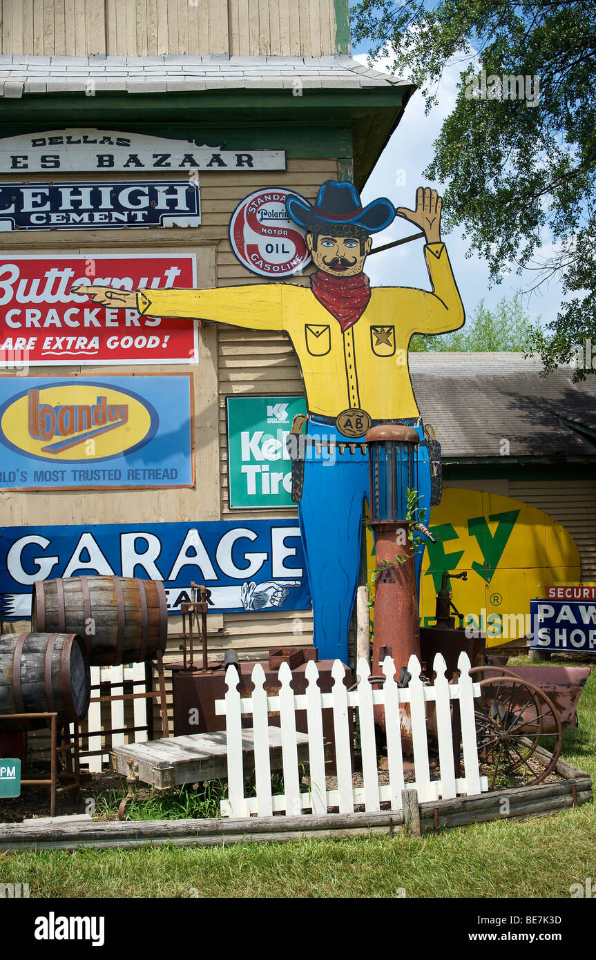 a pointing sign cowboy in a junk variety yard - Stock Image