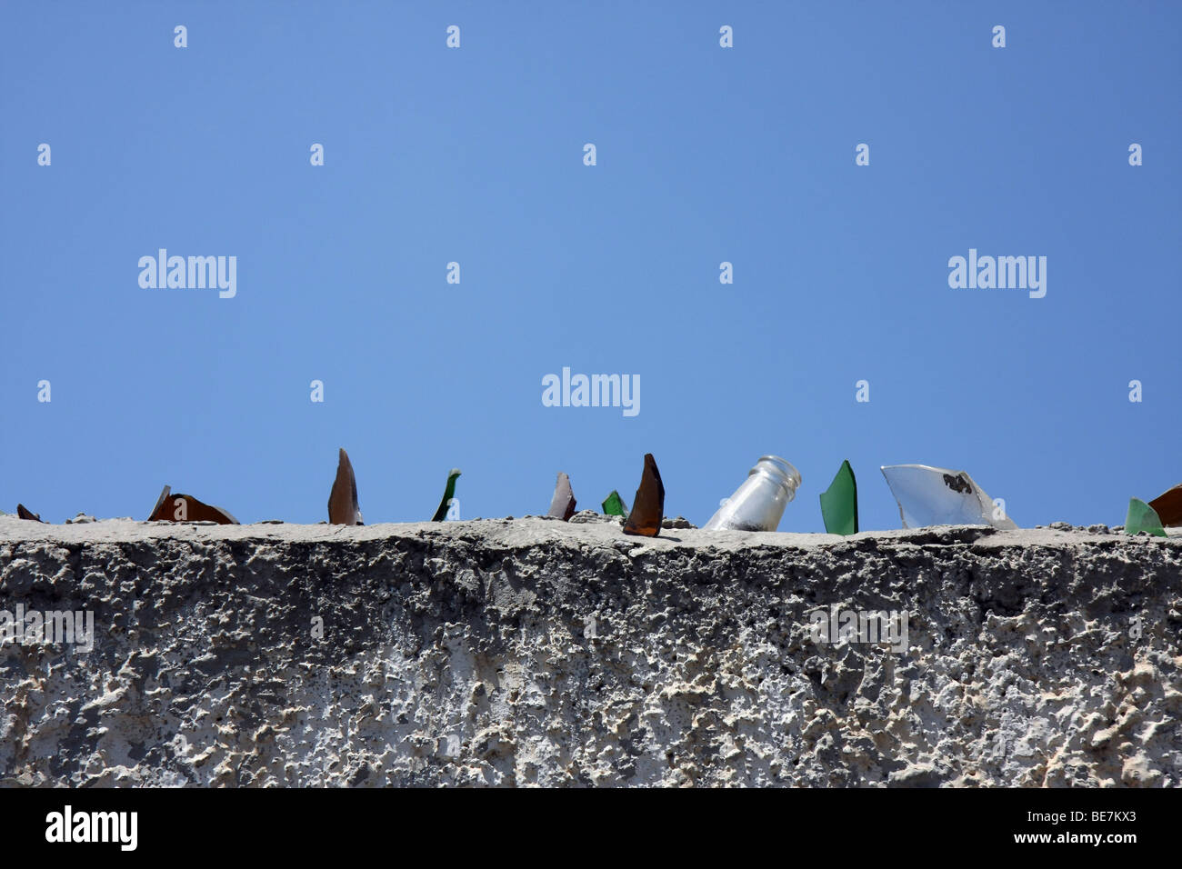 Top of a wall with sharp glass fragments from broken bottles as protection against people climbing over the wall, - Stock Image