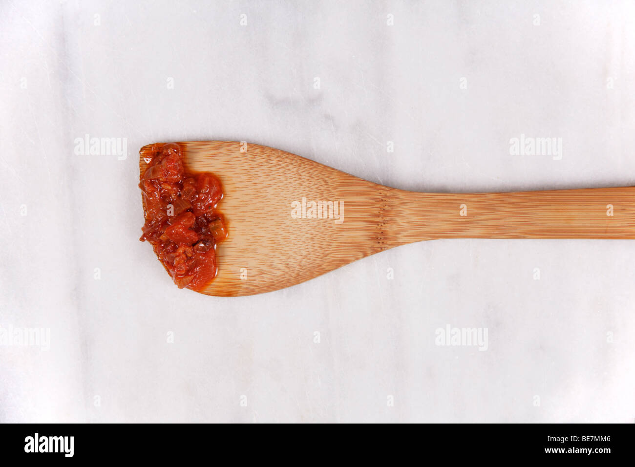 Tomato fondue sauce on a wooden spatula - Stock Image