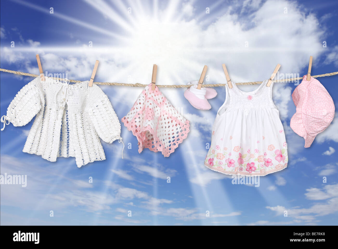 Adorable Baby Girl Clothes Hanging Outdoors - Stock Image