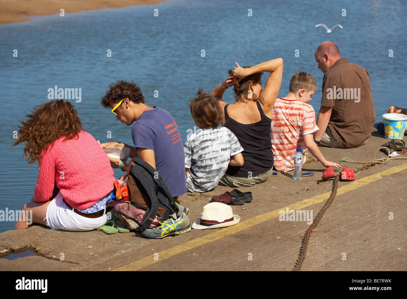 Holidaymakers sitting on the Harbour Wall at Wells next the Sea in North Norfolk - Stock Image