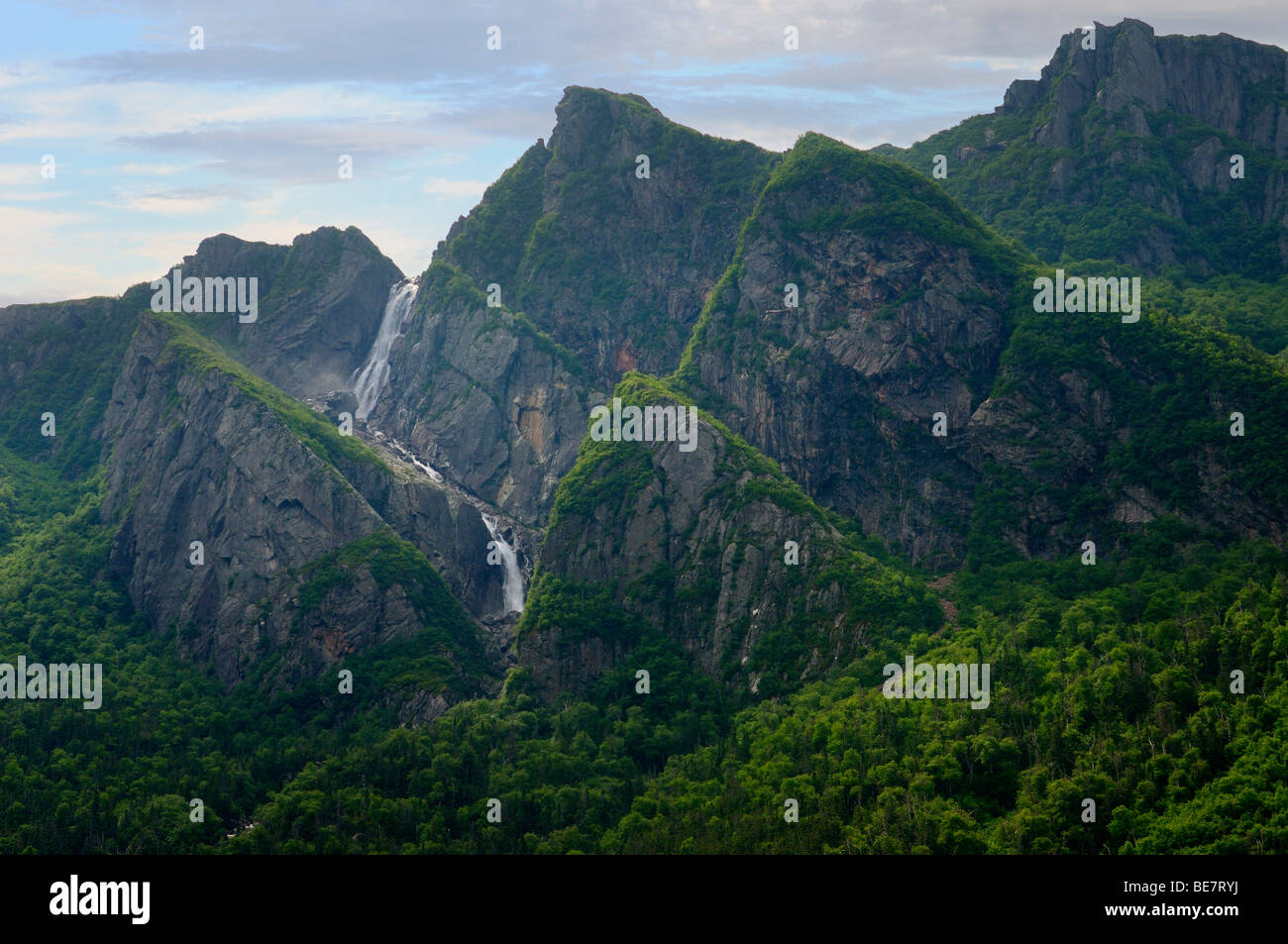 Waterfalls plunging into Western Brook Pond with steep rock cliff at Gros Morne National Park Newfoundland - Stock Image