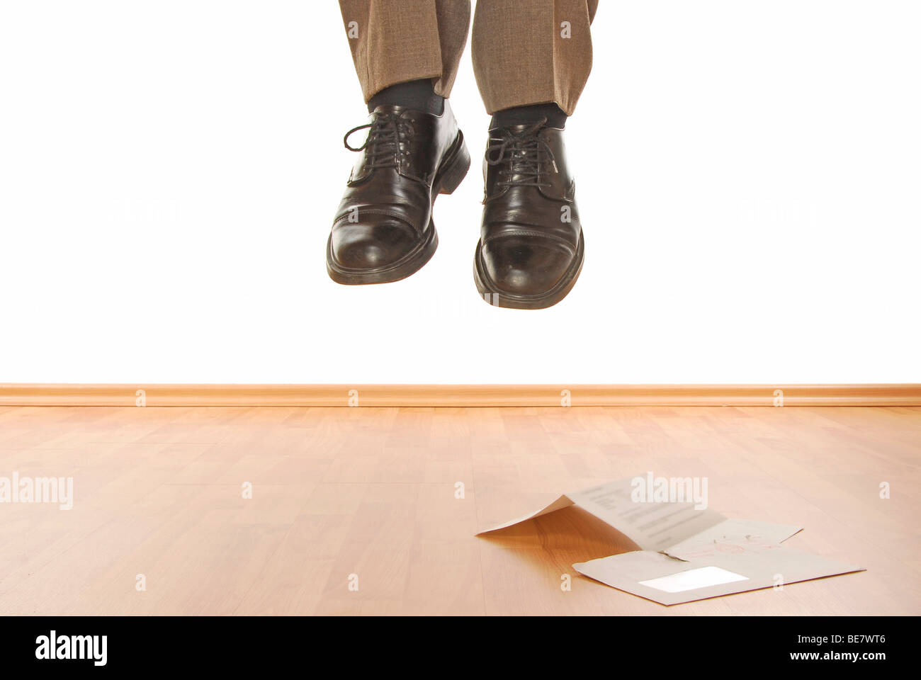 Hanged manager with an open letter, symbolic image for bad news - Stock Image