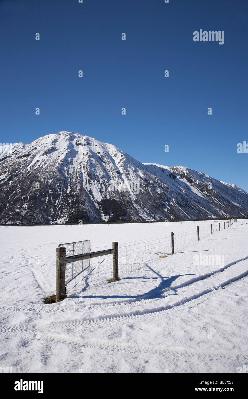 Fenceline, Farmland and Purple Hill with Snow, Arthur's Pass Road, Canterbury, South Island, New Zealand - Stock Image