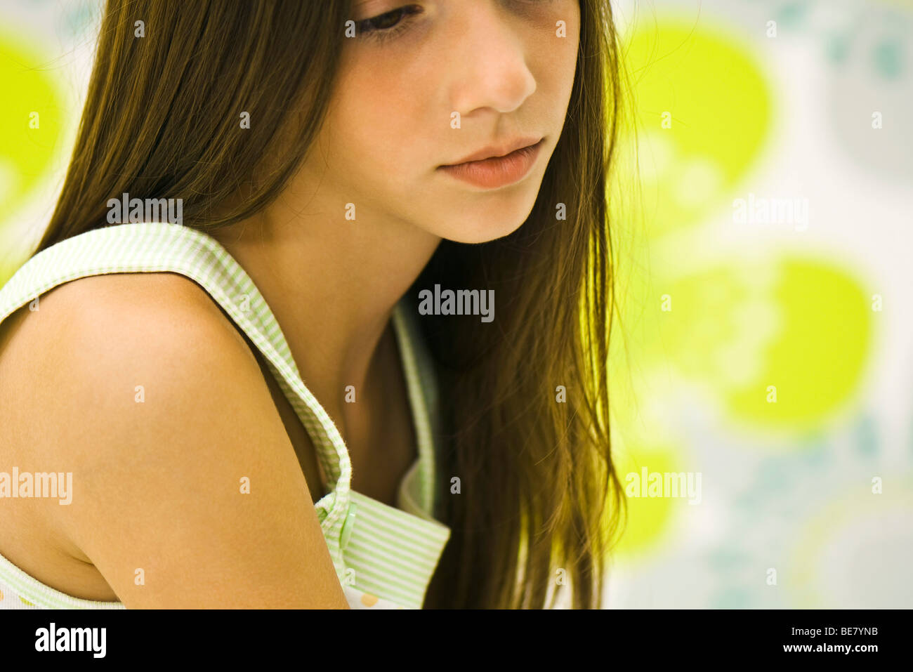 Girl contemplatively looking down - Stock Image