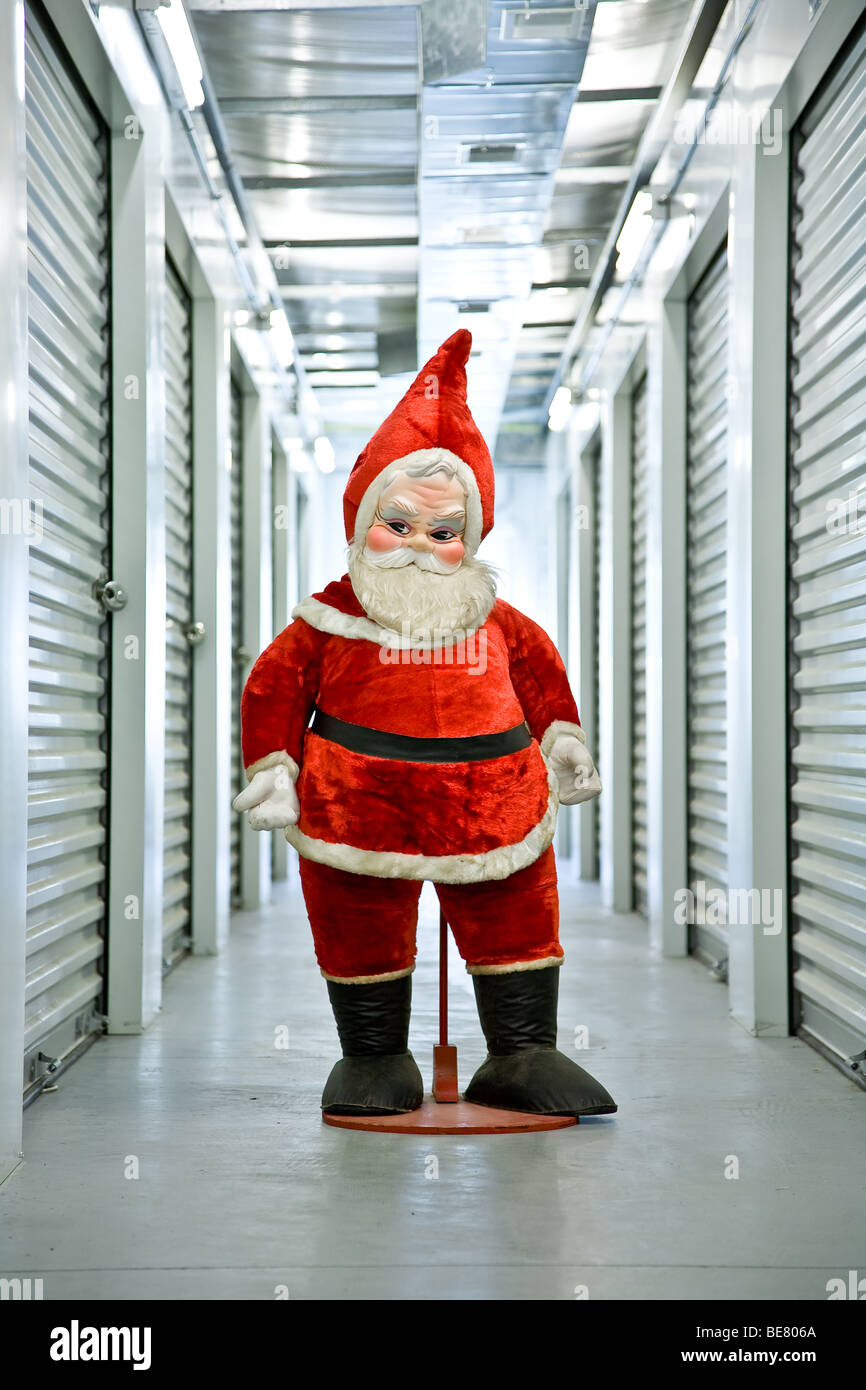 A 1960's era stuffed Santa Claus stands in an industrial hallway inside his self storage unit - Stock Image
