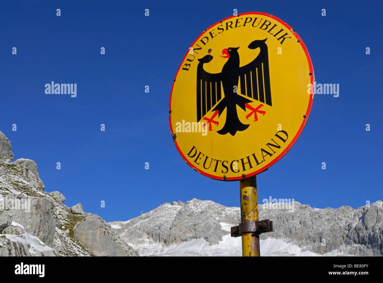 Sign of boarder Bundesrepublik Deutschland with Bundesadler at notch Gatterl with view to Zugspitze, Wetterstein Stock Photo