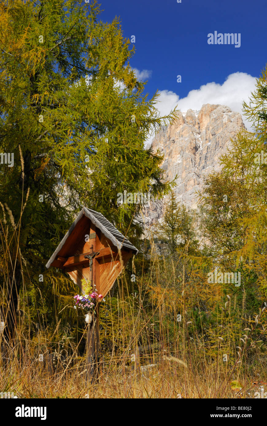Cross beneat Cristallo range with larches in autumn colours, Dolomites, South Tyrol, Italy Stock Photo