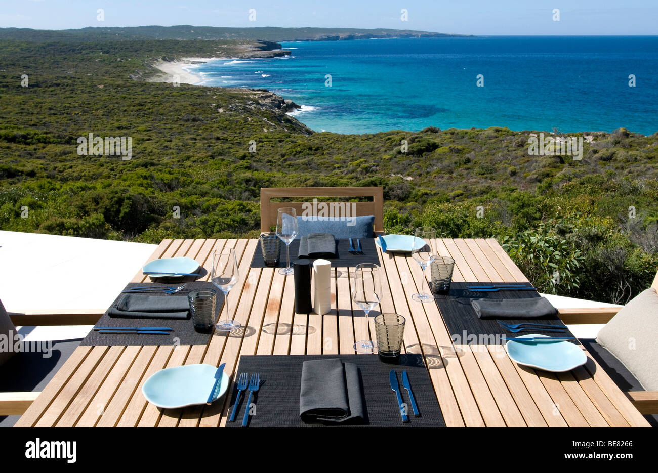 A table is laid on the terrace of the Southern Ocean Lodge with view at Hanson Bay, Kangaroo Island, South Australia, - Stock Image