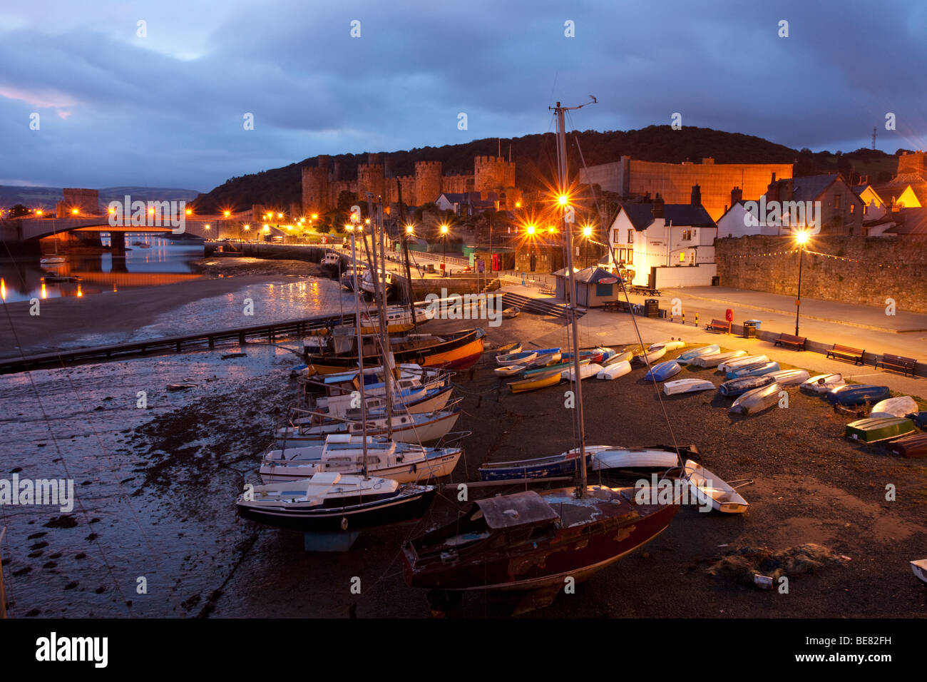 Conwy harbour scene before the morning light, with the streetlights shining on the boats and jetty. - Stock Image