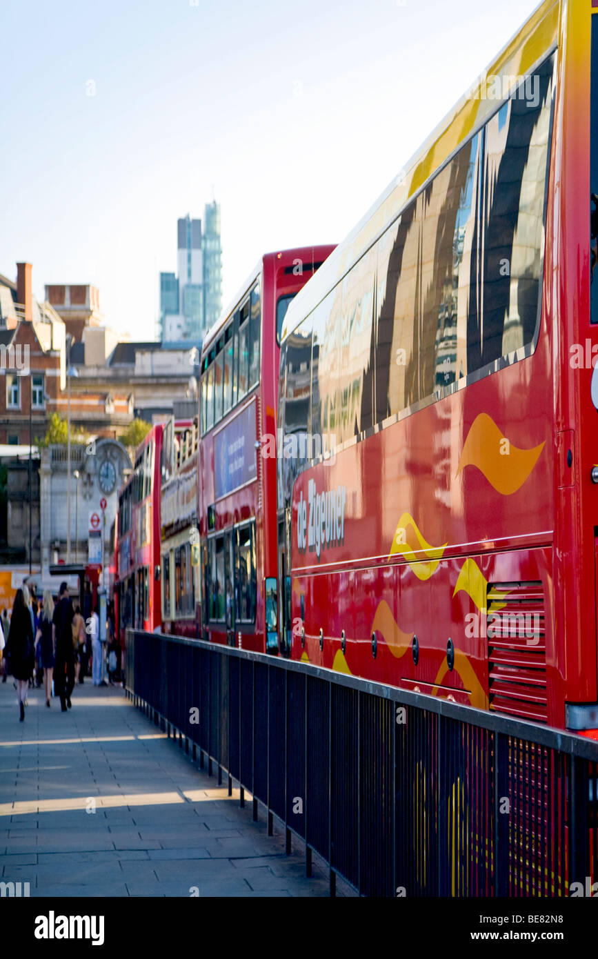 A view along London Bridge. Line of red buses and tourist coaches bumper to bumper in afternoon traffic. London. - Stock Image