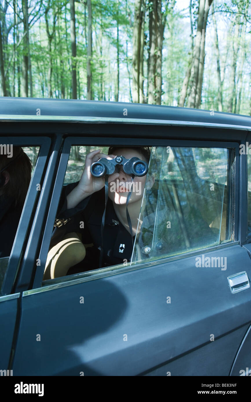 Woman sitting in car, looking out window through binoculars - Stock Image