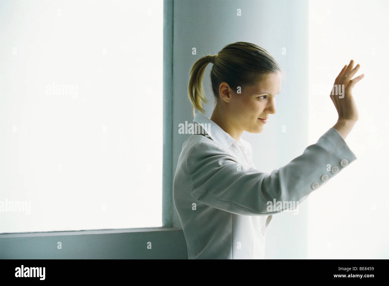 Woman waving, side view - Stock Image