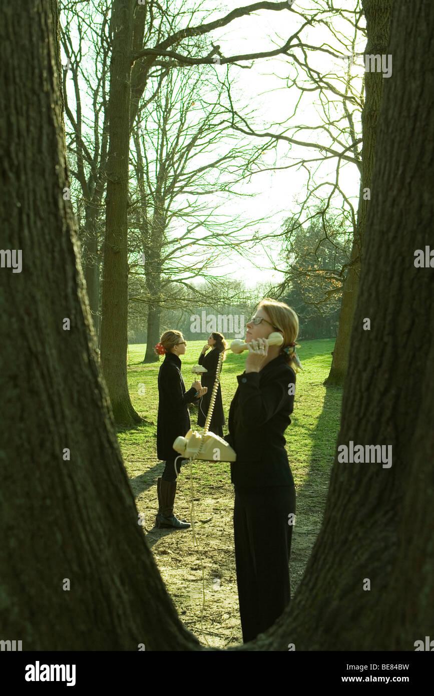 Females standing outdoors, using landline phones, viewed through tree trunks - Stock Image