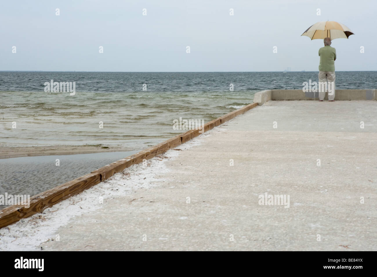 Man standing at end of pier, holding up umbrella, rear view - Stock Image