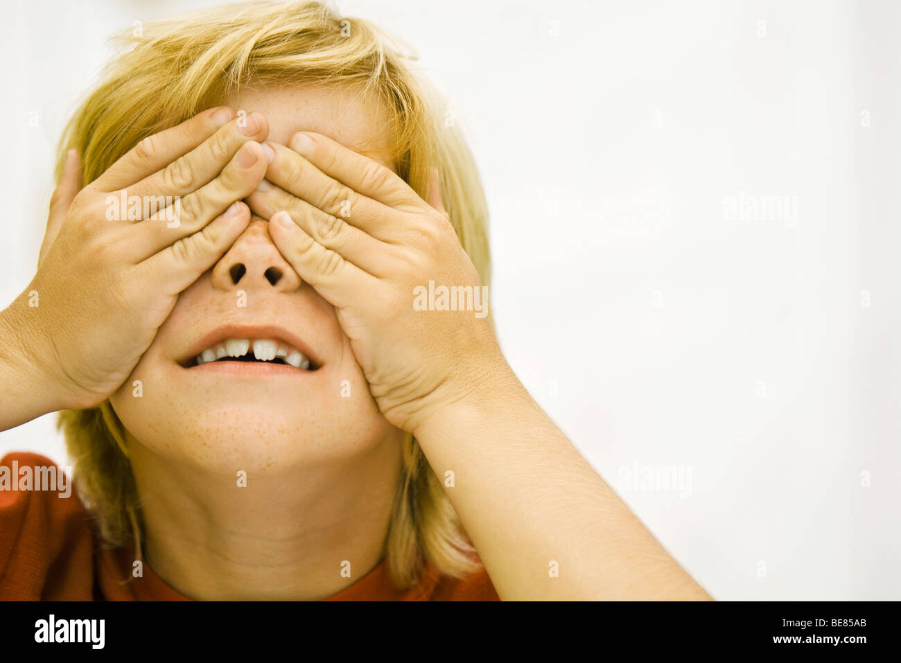 Boy covering eyes with hands - Stock Image