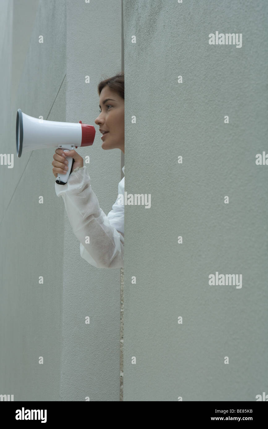 Woman speaking into megaphone, side view - Stock Image