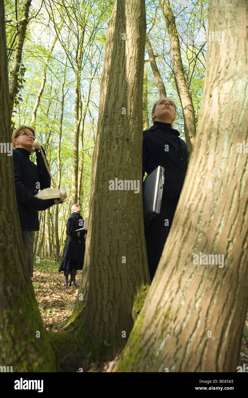Three women standing in woods, two holding laptop computers, the other using landline phone - Stock Image