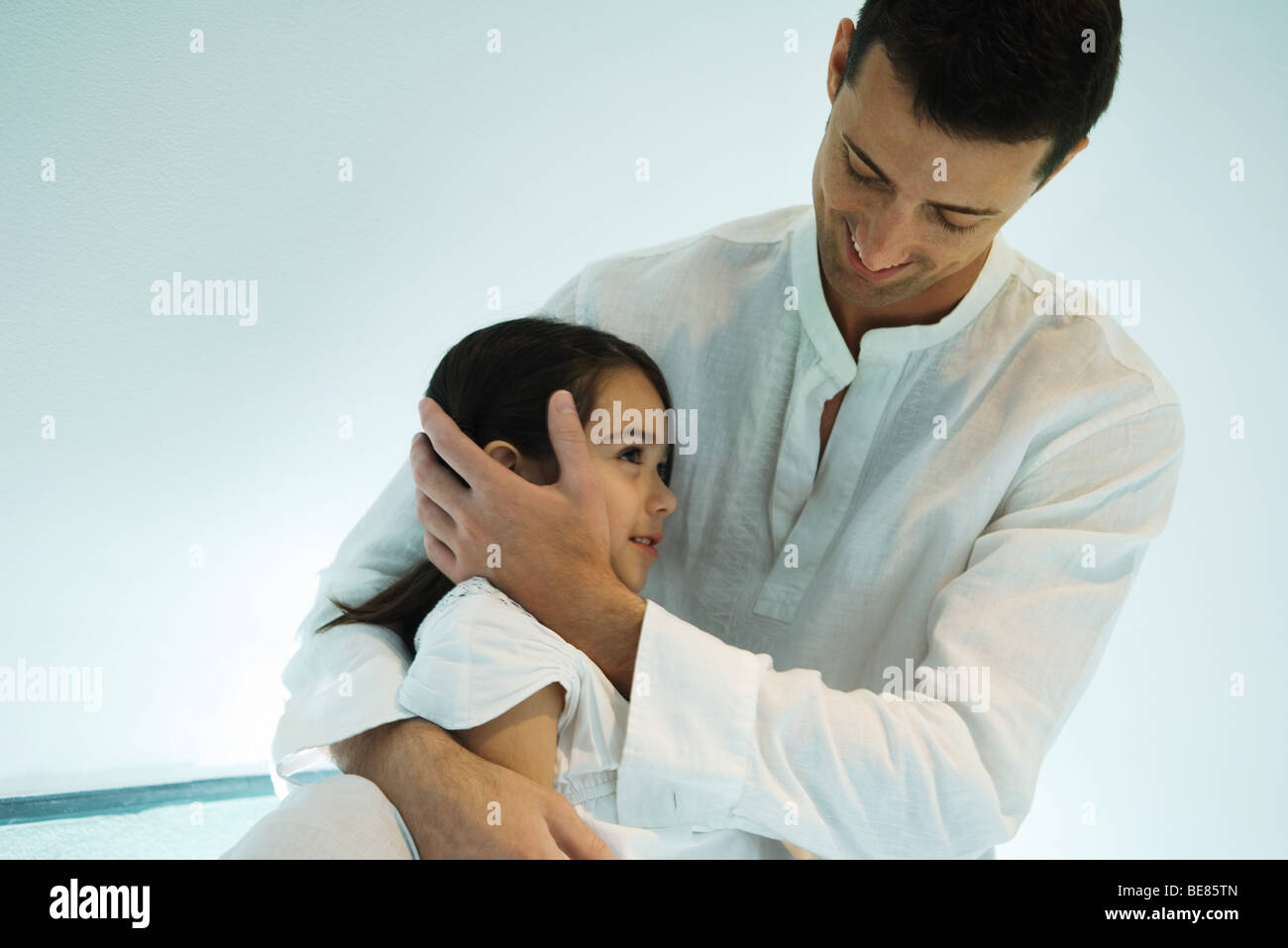Father embracing daughter, smiling - Stock Image
